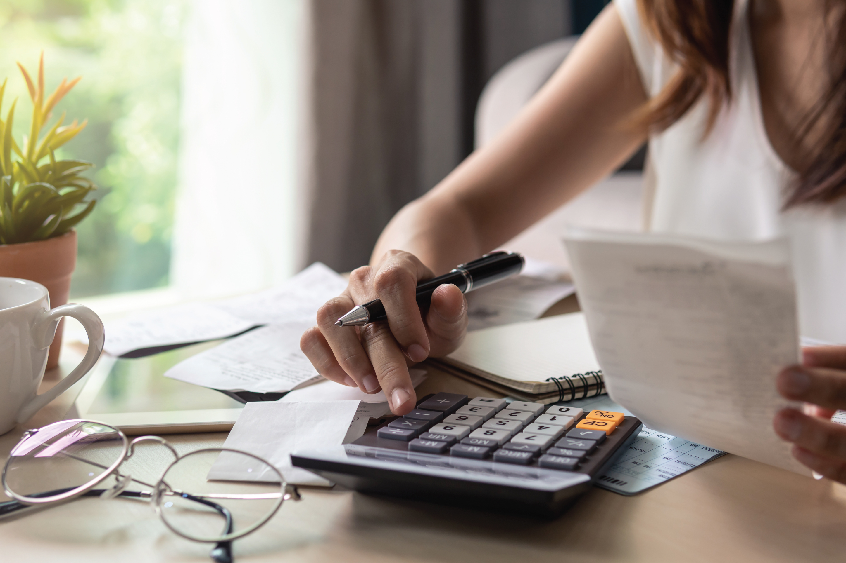 woman using calculator to budget her finances